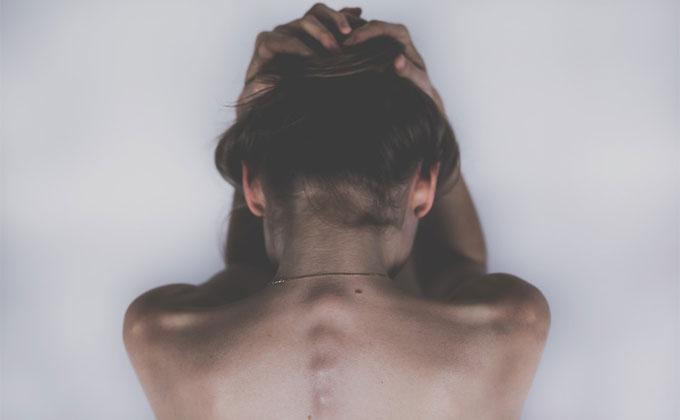 頭を抱えて落ち込む女性