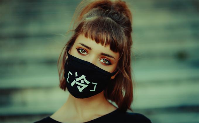 ウイルス対策で黒いマスクを着用する女性